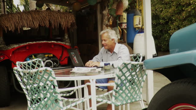 vídeos y material grabado en eventos de stock de ms man using laptop on outdoor table then leaves, laguna beach, california, usa - laguna beach california