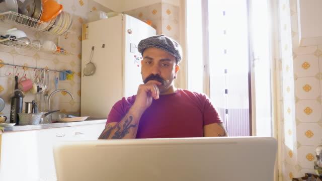 man using laptop - flat cap stock videos & royalty-free footage
