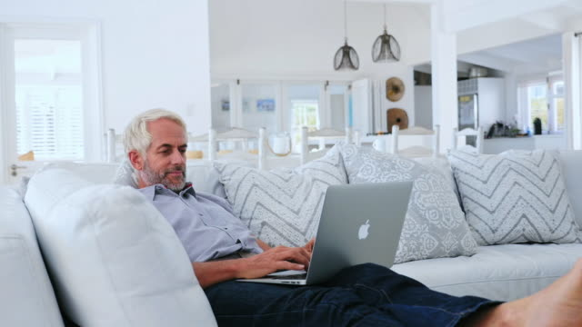 Man using laptop, woman sitting on sofa
