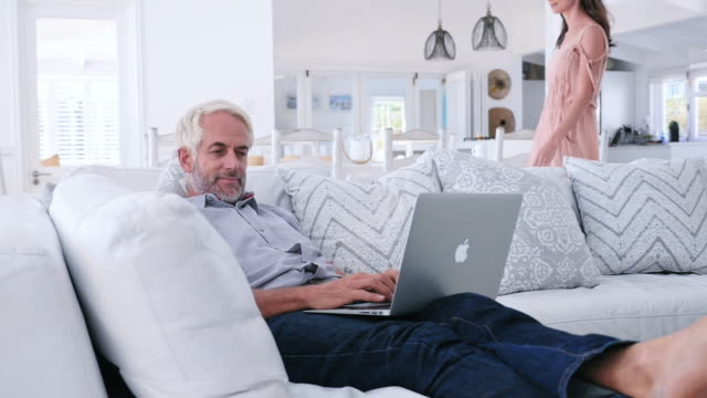 vídeos y material grabado en eventos de stock de man using laptop, woman walking in living room - 55 59 años