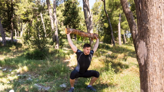 WS man using log for gym exercise in nature