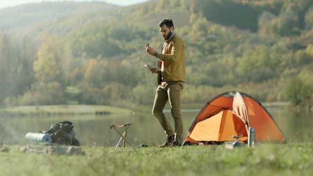 mann mit karte und kompass auf camping-ausflug am see - kompass stock-videos und b-roll-filmmaterial
