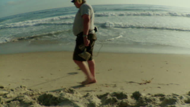 vídeos de stock, filmes e b-roll de ws man using metal detector on beach / laguna beach, california, usa - kelly mason videos