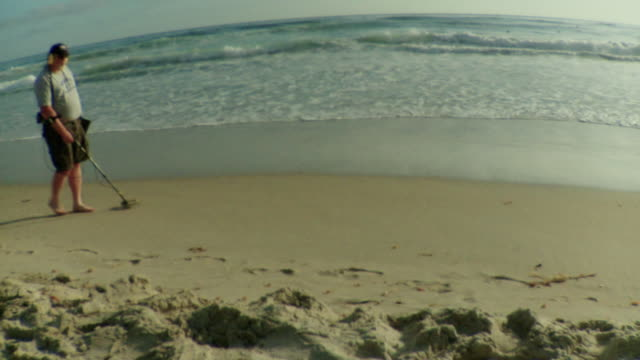 ws man using metal detector on beach / laguna beach, california, usa - kelly mason videos stock videos & royalty-free footage