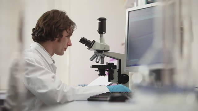 CU Man using microscope in laboratory / Leeds, West Yorkshire, UK