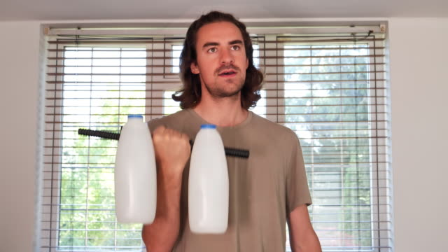 man using milk as weights. - competition stock videos & royalty-free footage