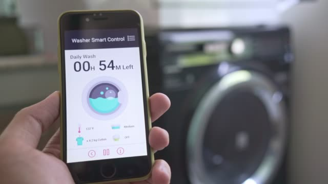 man using mobile application to control washing machine - home automation stock videos & royalty-free footage