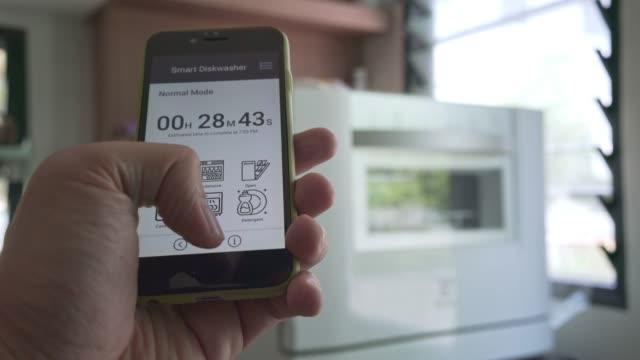 mann mit mobiler applikation-touchscreen zur steuerung der geschirrspülmaschine - spülmaschine stock-videos und b-roll-filmmaterial