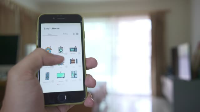 Man using mobile application touch screen to control lighting in the living room