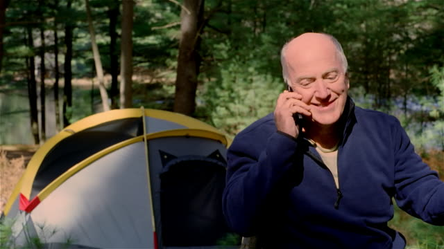 CU, man using mobile phone at camping site, USA, Pennsylvania, Solebury