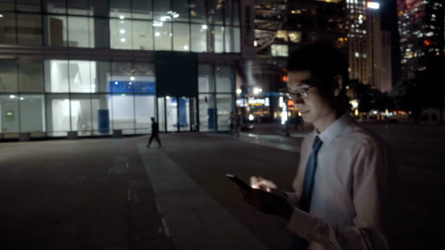 Man using mobile phone at night in the city