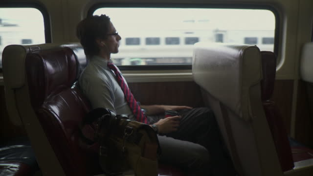 WS Man using mobile phone, drinking coffee and listening music in train / New York City, New York, USA