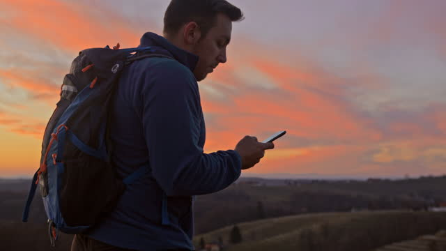 man using mobile phone for direction on mountain landscape - text messaging stock videos & royalty-free footage