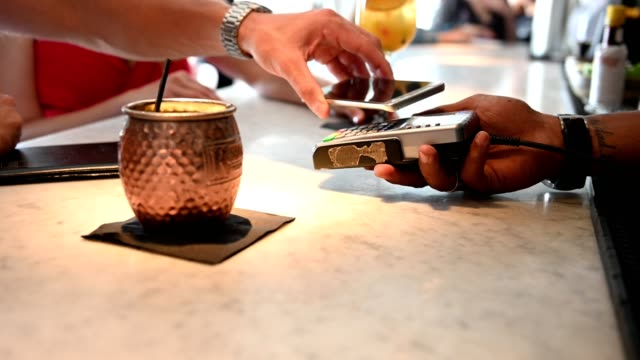 man using mobile phone for payment at bar counter - near field communication stock videos & royalty-free footage