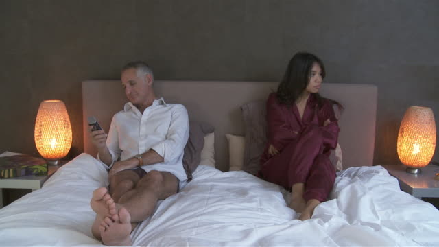 vidéos et rushes de ws man using mobile phone on bed, unhappy woman sitting with arms crossed / brussels, belgium - pyjama