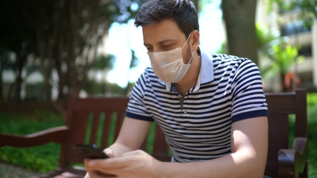 man using mobile phone on park bench - wearing face mask - bench stock videos & royalty-free footage