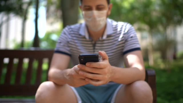 man using mobile phone on park bench - wearing face mask - park bench stock videos & royalty-free footage