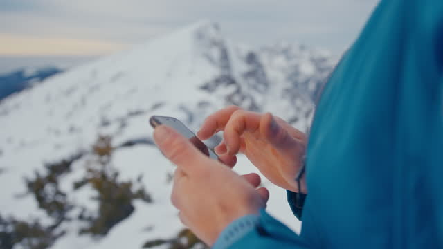 vídeos y material grabado en eventos de stock de hombre usando teléfono móvil en montaña nevada - nevosa
