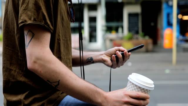 mann mit handy während der sitzung auf geländer - tasse oder becher stock-videos und b-roll-filmmaterial
