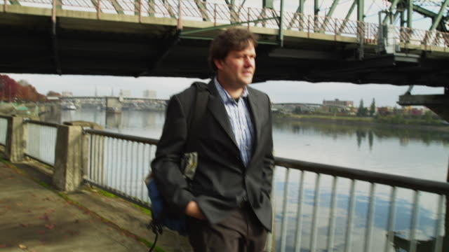 ms ts man using mobile phone while walking, hawthorne bridge in background / portland, oregon, usa - see other clips from this shoot 1695 stock videos & royalty-free footage