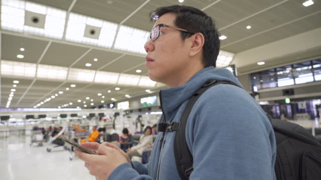 man using phone and looking at flight schedule at airport. - large scale screen stock videos & royalty-free footage
