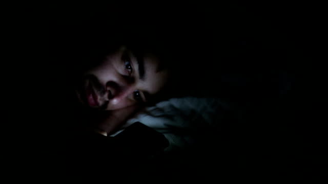man using phone at night, panning to alarm clock. - reclining stock videos and b-roll footage