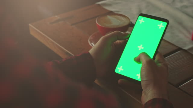 man using phone with green screen hold in hands stock video - over the shoulder stock videos & royalty-free footage