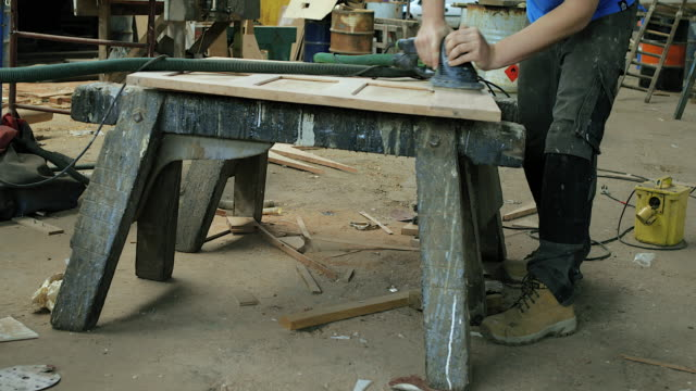 CU Man using power tool to sand wood in workshop