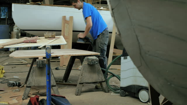 PAN Man using power tool to sand wood in workshop