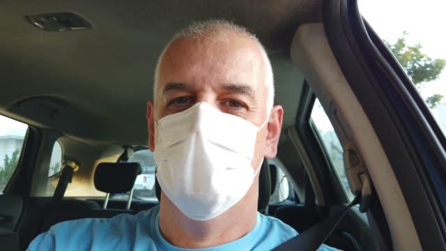 vídeos de stock, filmes e b-roll de homem usando máscara facial protetora em um carro. - moving image