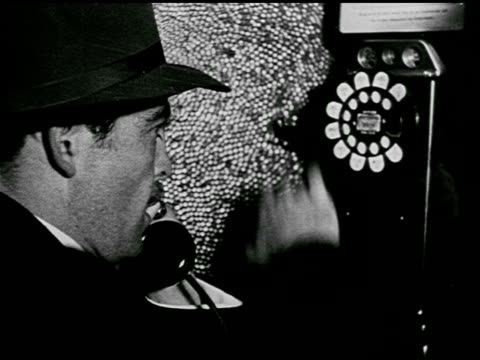 man using public pay phone in telephone booth, dialing operator, rotary dial, pulling on hook switch. operators working switchboard, pushing cord... - telephone booth stock videos & royalty-free footage