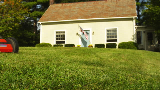 CU Man using push lawn mower in front yard of house, low section, Manchester, Vermont, USA