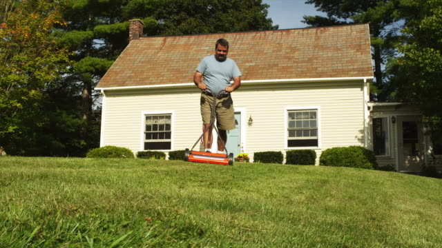 ws cu man using push lawn mower in front yard of house, manchester, vermont, usa - tagliaerba video stock e b–roll