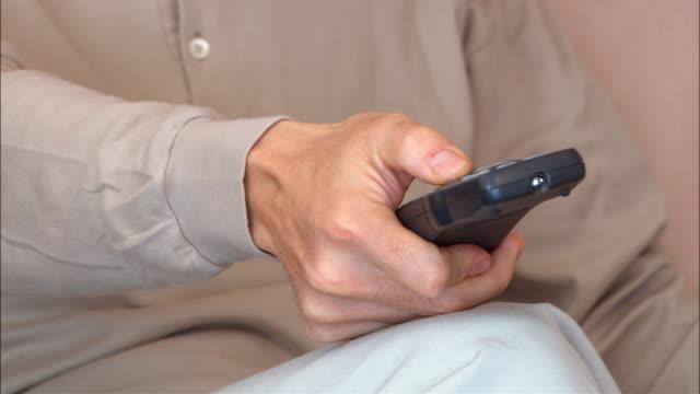 cu, man using remote control, mid section - テレビのリモコン点の映像素材/bロール
