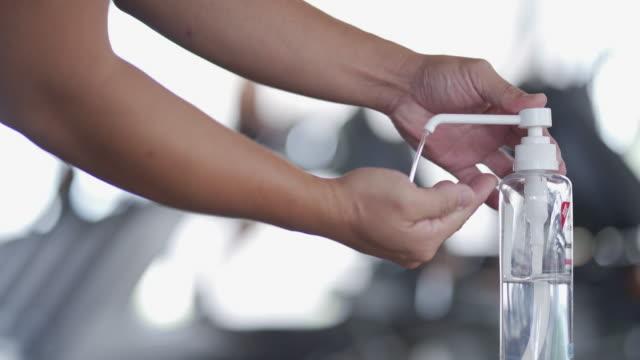 vídeos de stock, filmes e b-roll de homem usando desinfetante para limpar as mãos antes de se exercitar na academia. - equipamento para exercícios