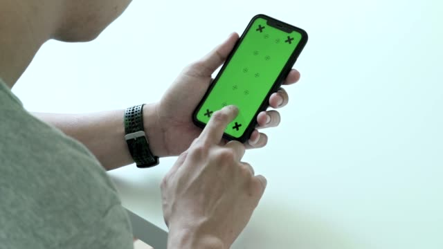 man using, scrolling and looking smart phone green screen with chroma key at home - human hand stock videos & royalty-free footage