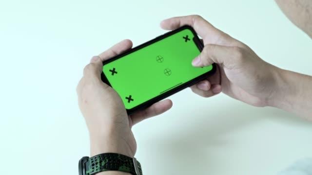 man använder, rullning och ser smart telefon grön skärm med chroma key hemma - över axel perspektiv bildbanksvideor och videomaterial från bakom kulisserna