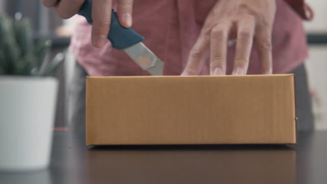 man using sharp knife cutting and opening box package from his online shopping - cardboard box stock videos & royalty-free footage