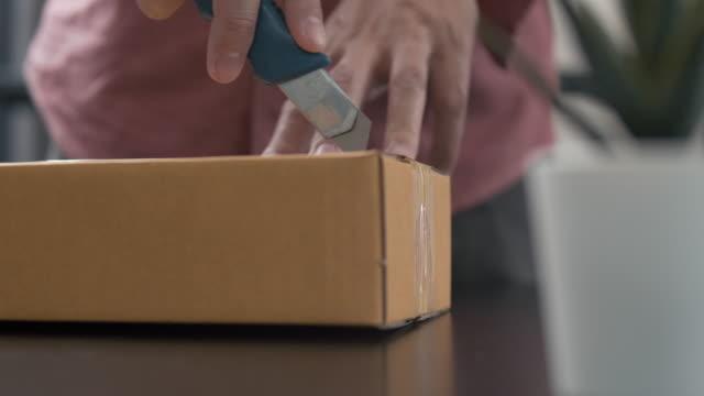 vídeos y material grabado en eventos de stock de hombre usando el corte de cuchillo afilado y el paquete de la caja de apertura de sus compras en línea - caja