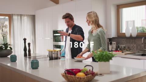 vídeos y material grabado en eventos de stock de hombre usando un dispositivo inteligente mientras cocina comida en casa - cocina electrodomésticos