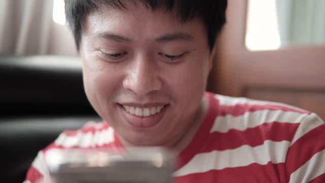 vídeos de stock, filmes e b-roll de homem usando telefone inteligente em casa. - só um adulto de idade mediana