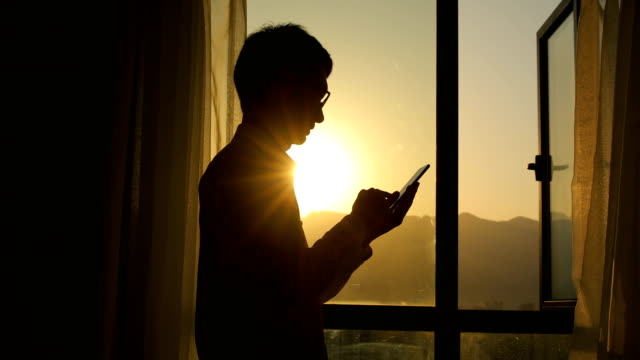 man using smart phone at sunset - control stock videos & royalty-free footage