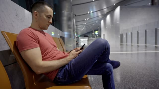man using smart phone at the airport - gulf countries stock videos & royalty-free footage