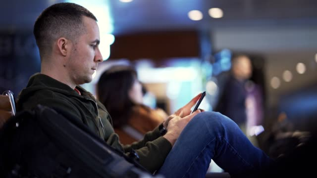 man using smart phone at the airport - qatar stock videos & royalty-free footage