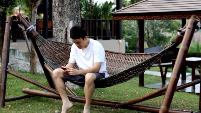 man using smart phone at the wood hammock garden view