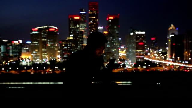 Man using smart phone in city night