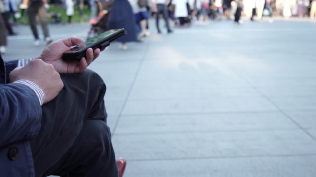 公共エリアでスマートフォンを使用している男性。 - 待つ点の映像素材/bロール
