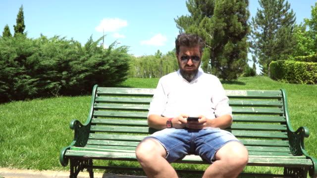 公園でスマート フォンを使用している人