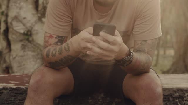 vídeos de stock, filmes e b-roll de cu de homem usando telefone inteligente no parque. - mão humana