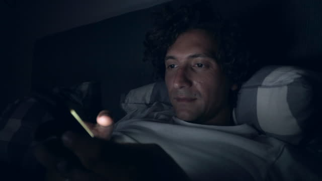 vídeos de stock e filmes b-roll de man using smart phone late in night. - cama